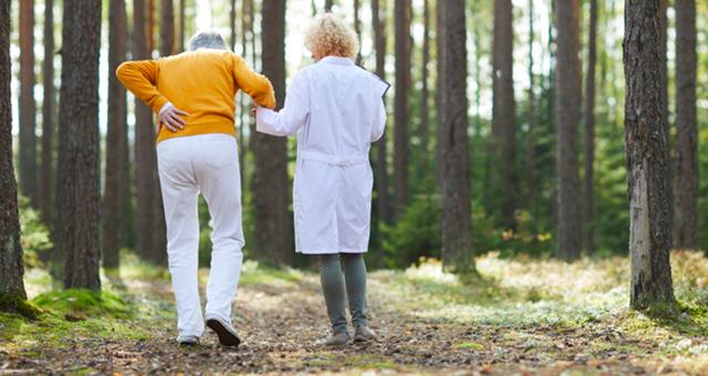 Anziano fragile che cammina sostenuto da una dottoressa.